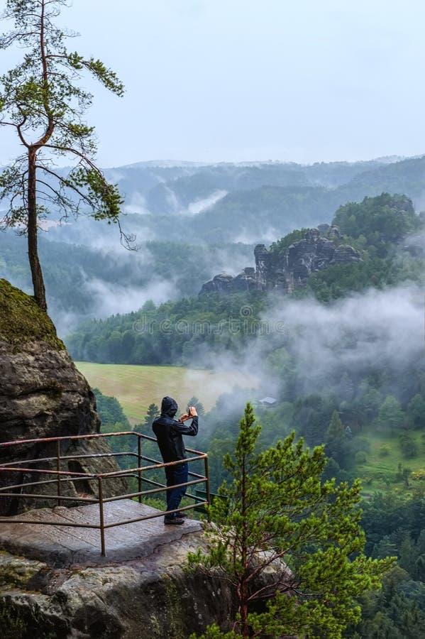 Das Schattenbild einer Person mit einem Telefon steht mit seinem zurück zu dem Fotografen auf dem Felsen und betrachtet die Berge lizenzfreies stockbild