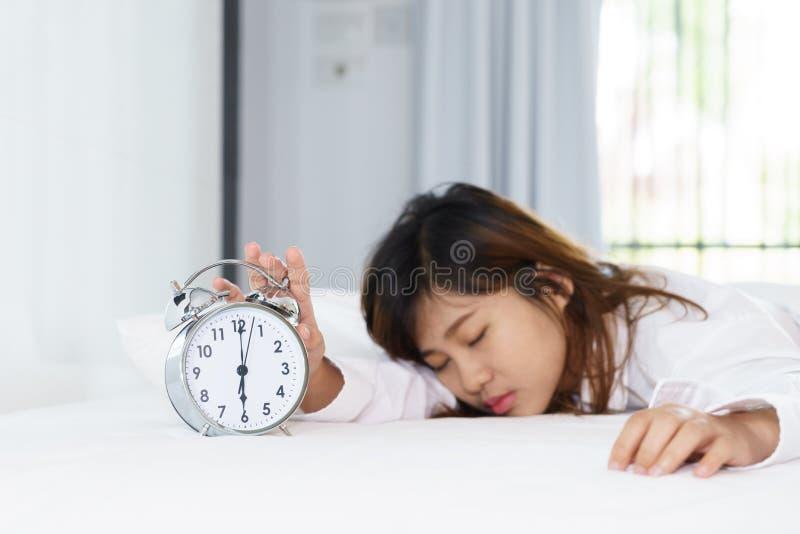 Das schläfrige Frauenversuchen stellen Wecker ab lizenzfreie stockfotografie