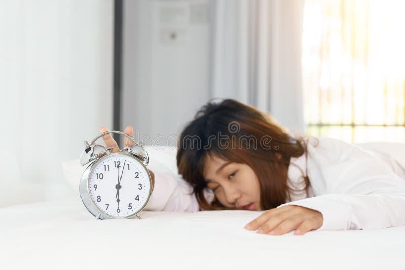 Das schläfrige Frauenversuchen stellen Wecker morgens ab stockfoto
