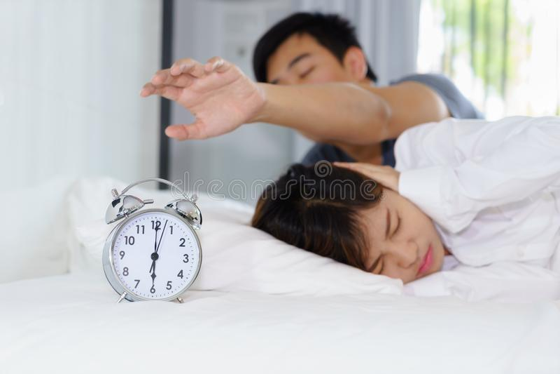 Das schläfrige Mannversuchen stellen Wecker neben einer Frau ab, die vorbei gestört wird stockbilder
