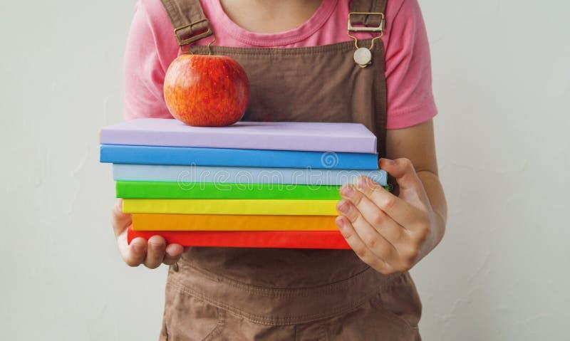 Das Schulmädchen hält Bücher und einen Apfel Hände des Kindes stockbild