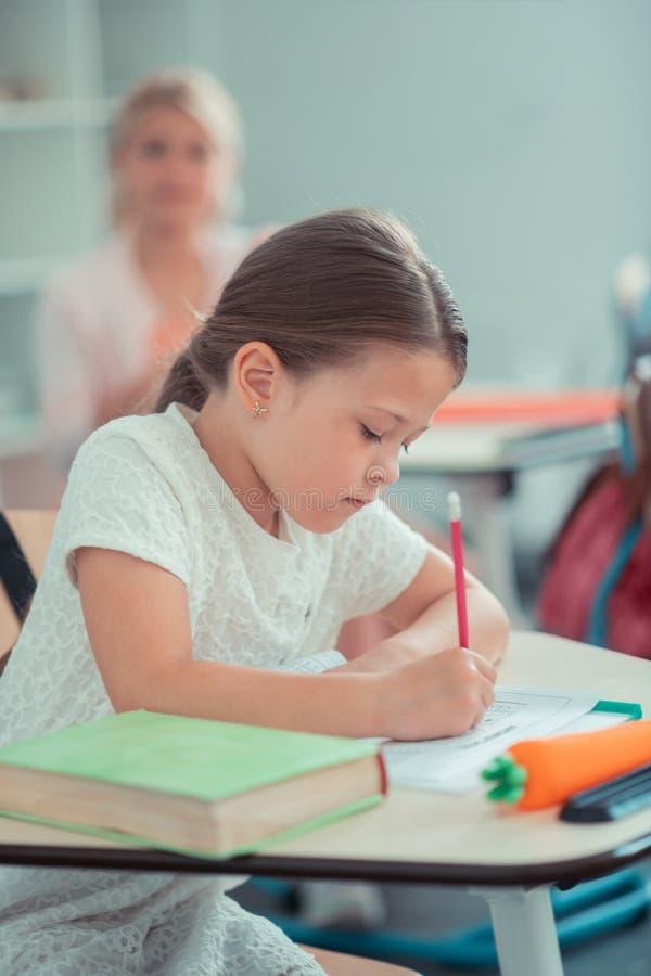 Das Schulmädchen, das stark an ihrem Mathe arbeitet, prüfen stockfotos