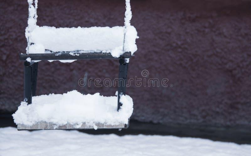 Das Schwingen der Kinder bedeckte Schnee im Winter, Abschluss oben lizenzfreie stockfotografie