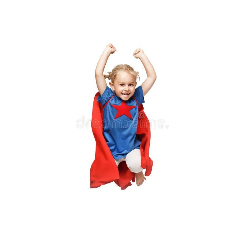 Das sehr aufgeregte kleine Mädchen kleidete wie das Heldspringen lokalisiert auf weißem Hintergrund an stockfoto