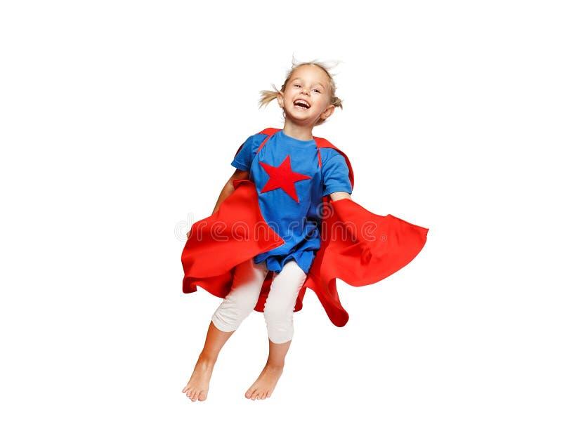 Das sehr aufgeregte kleine Mädchen kleidete wie das Heldspringen lokalisiert auf weißem Hintergrund an lizenzfreie stockbilder