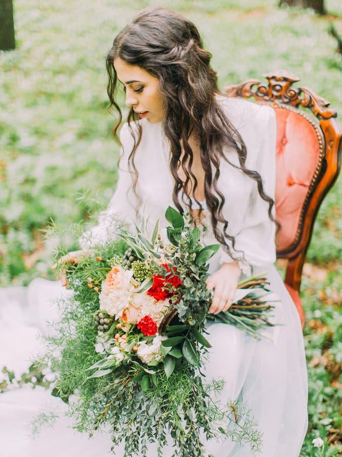 Das Seitenporträt der Frau mit dem langen gelockten Haar im weißen Hochzeitskleid, Holding der bunte Blumenstrauß und stockfoto