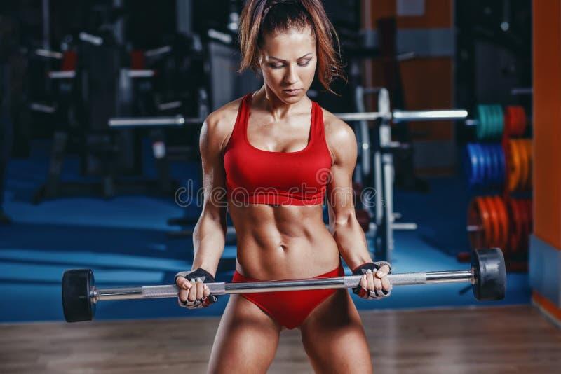 das sexy junge Leichtathletikmädchen, das Bizeps Barbelllocke tut, trainiert in der Turnhalle lizenzfreie stockbilder