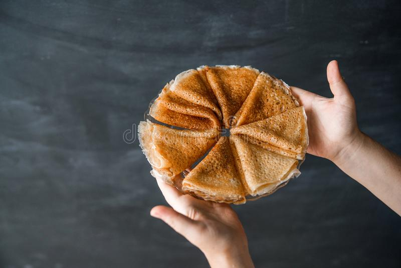 Das Shrovetide-Konzept Ein Stapel gefaltete Pfannkuchen auf einer Platte in den weiblichen Händen auf einer schwarzen Tafel gegen lizenzfreies stockfoto