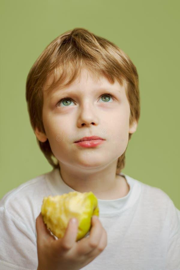 Das siebenjährige Kind und der Apfel stockbild