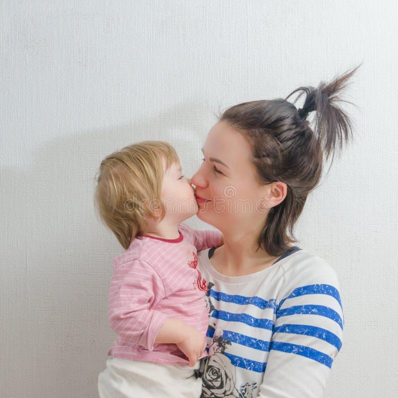 Das Sitzen auf meinem Handbaby küsst Mama lizenzfreie stockfotos