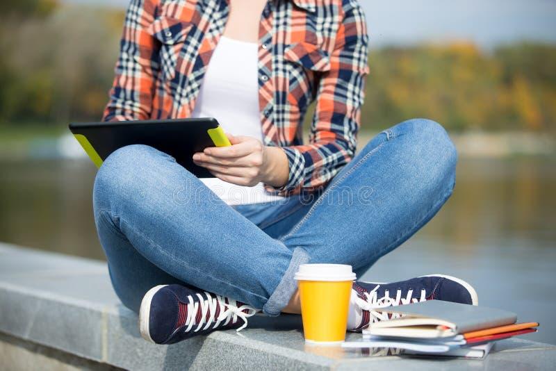 Das sitzende Türkische des Studenten an der Brücke mit Tablette lizenzfreies stockbild