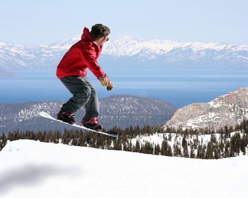 Das Snowboarderspringen stockfotos