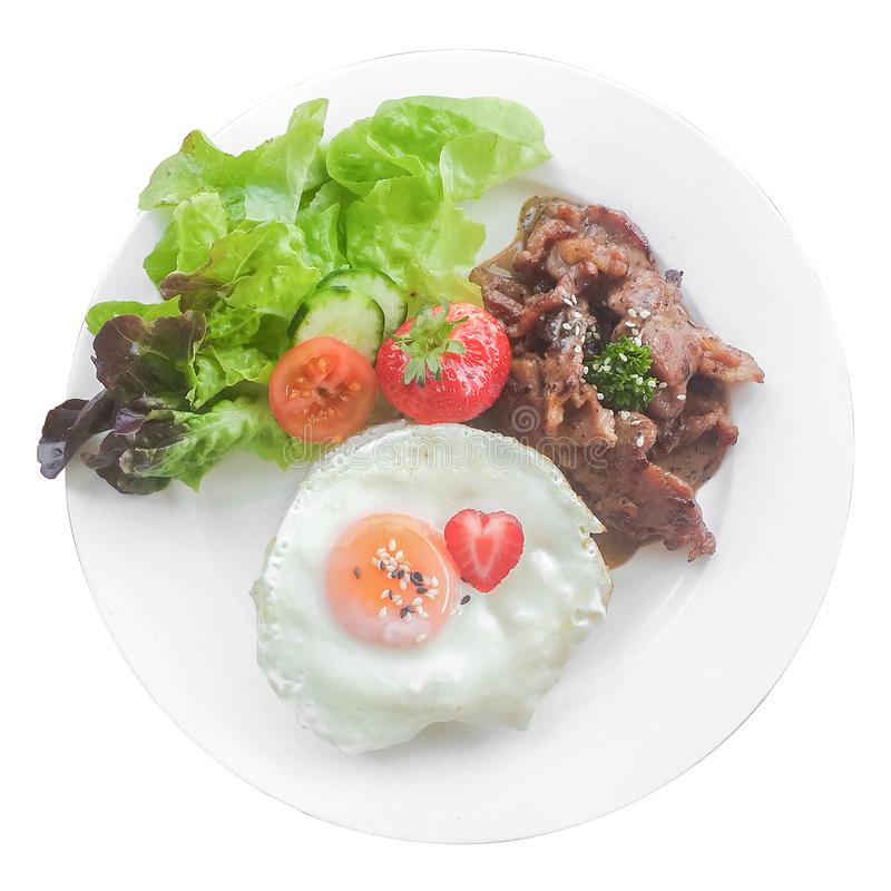 Das Spiegelei mit Schweinefleischsteak-Fleischabendessen mit Erdbeere-friut und Salat in Teller lokalisiertem weißem Hintergrund stockfotos