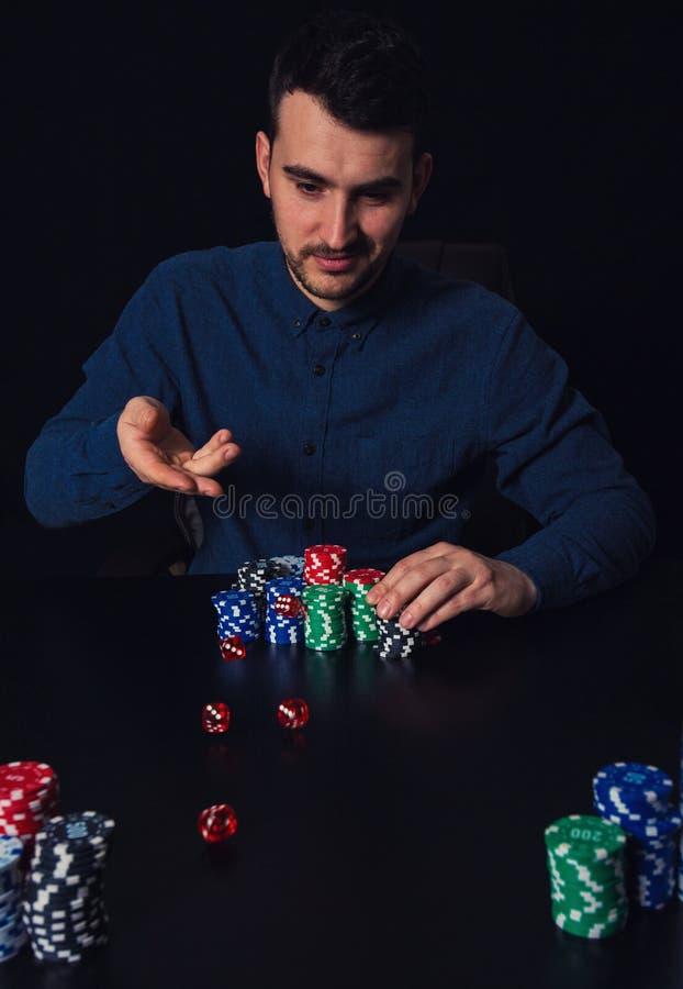 Das Spielerwerfen des jungen Mannes würfelt gesetzt am Kasinotisch Versuchendes Glück des süchtigen Kerls, Chips wettend und spie stockfoto