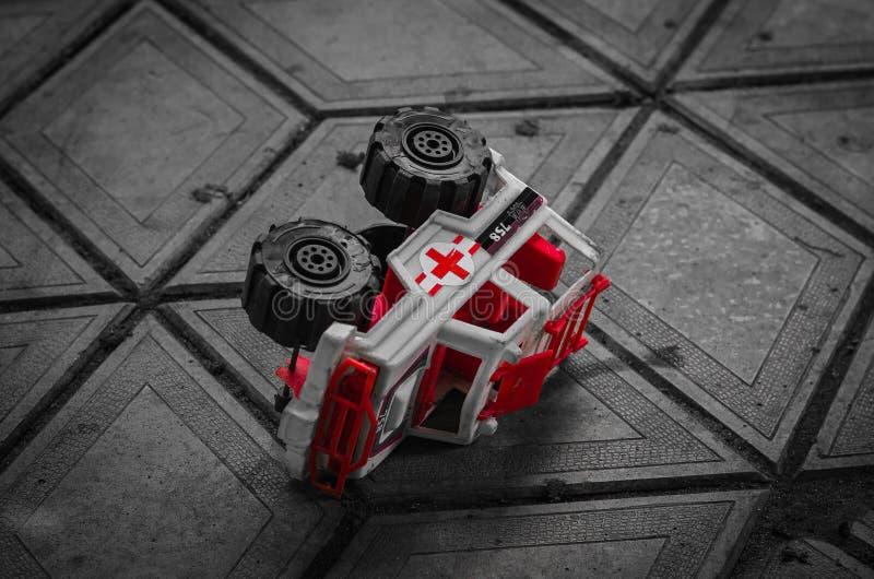 Das Spielzeug der Kinder liegt auf dem Pflasterstein, der harmonisch in seine Linie passt Eine interessante Kombination von Farbe lizenzfreie stockbilder