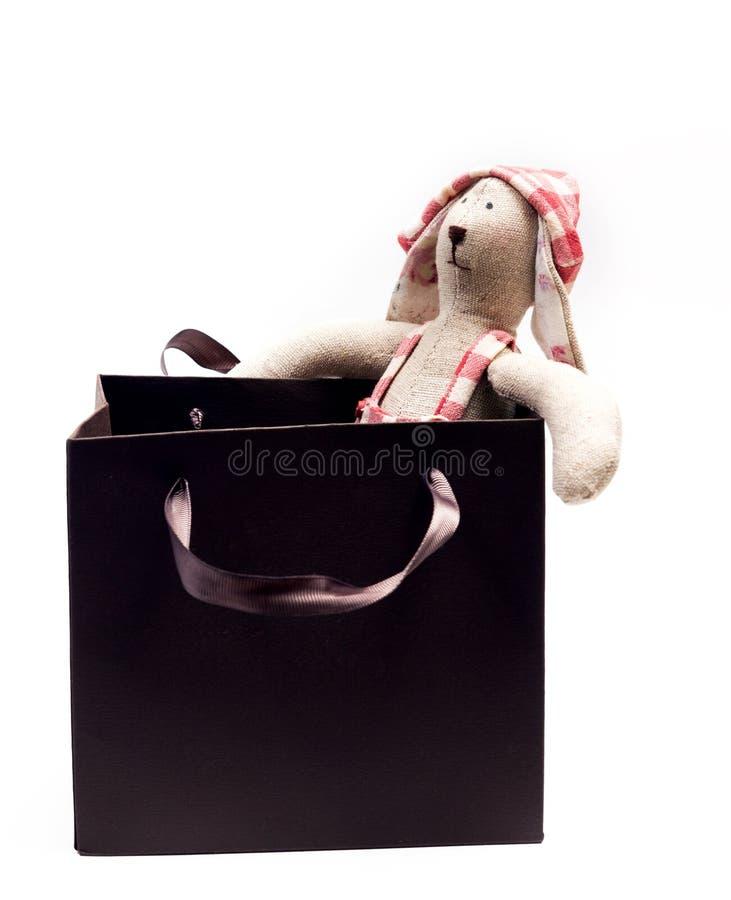 Das Spielzeugkaninchen in einem Hut sitzt in einem lokalisierten Geschenkbraunpaket stockbilder