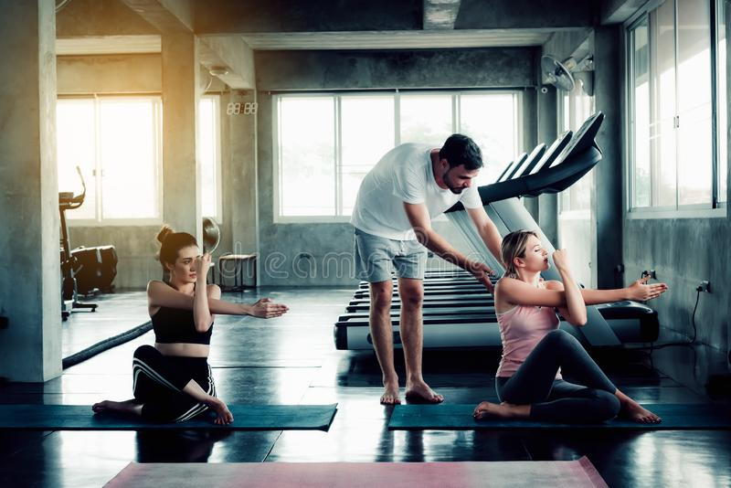 Das sportliche Frauengruppeyoga bildet mit Lehrer in der Eignungsturnhalle aus Lektion von Yogapraxis exercing, Porträt von attra lizenzfreie stockbilder