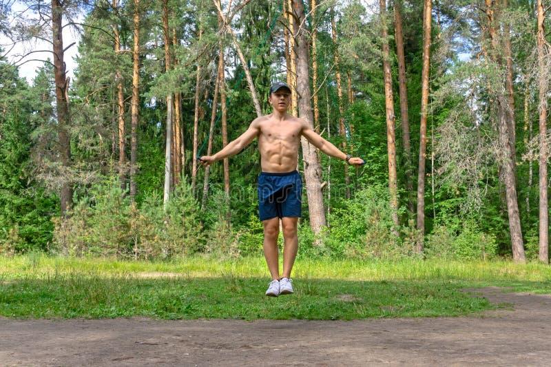 Das Springen des jungen Mannes fangen einen Kiefernwald ein stockfoto