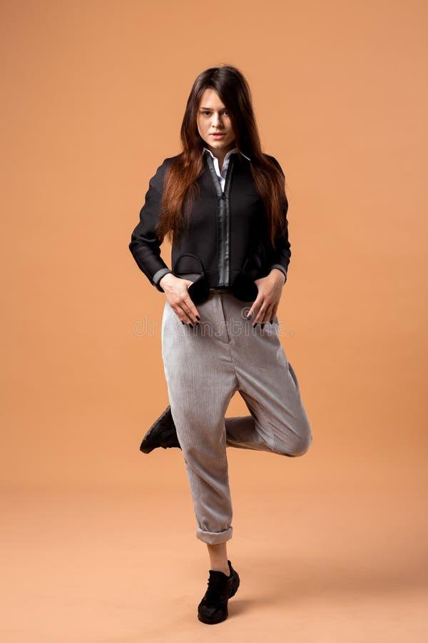 Das stilvolle dunkelhaarige Mädchen, das im weißen Hemd, in der grauen Hose, in der schwarzen Jacke und in den schwarzen Turnschu stockfoto
