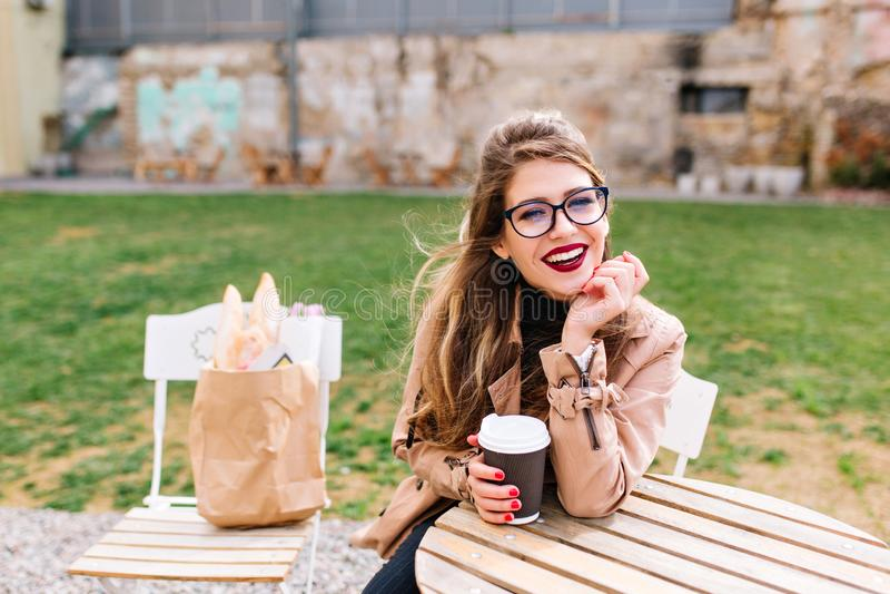 Das stilvolle langhaarige Mädchen, das braunen Mantel und Gläser trägt, nach dem Einkauf mit Taschen auf Stuhl trinkt Latte im Ca lizenzfreie stockfotos