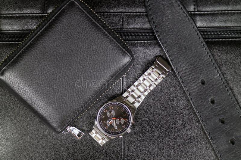 Das stilvolle Zubehör der Männer des schwarzen Leders, der Geldbörse, des Gurtes und der Stahluhr auf dem Hintergrund eines schwa lizenzfreie stockbilder