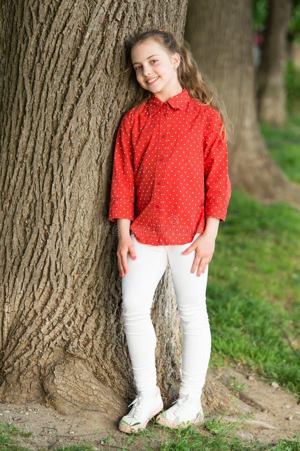 Das stilvollste Kind auf dem Spielplatz Glückliche stilvolle Kinderstellung am Baum Kleines Mode-Modell, das mit entzückendem läc stockbild