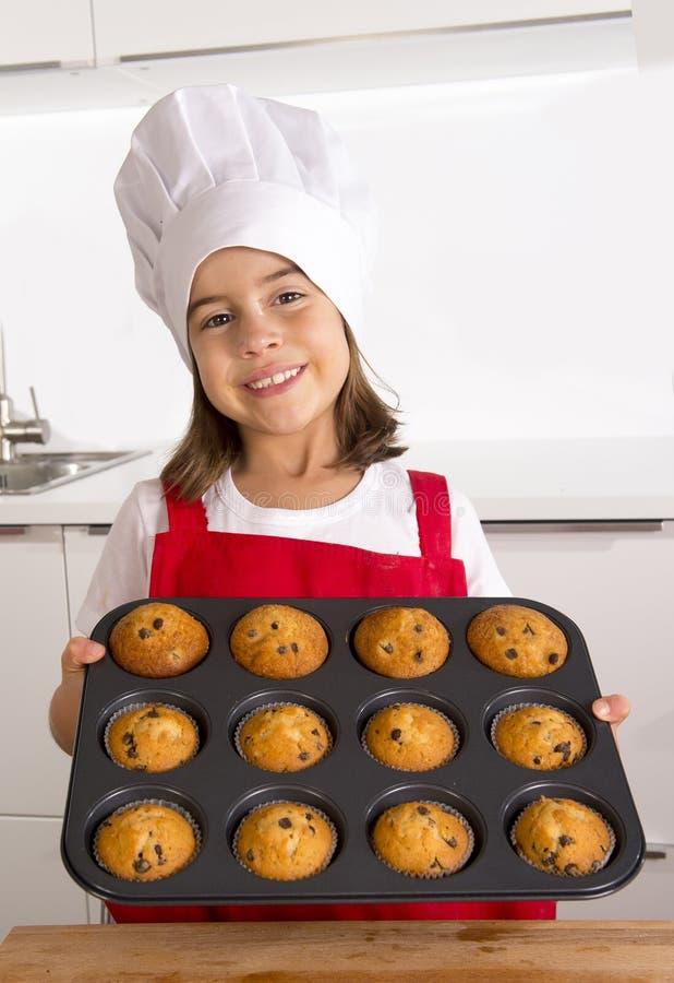 Das stolze weibliche Kind, das ihr selbst gemachtes Muffin darstellt, backt zusammen, das Backen lernend, welches das rote Schutz lizenzfreies stockbild