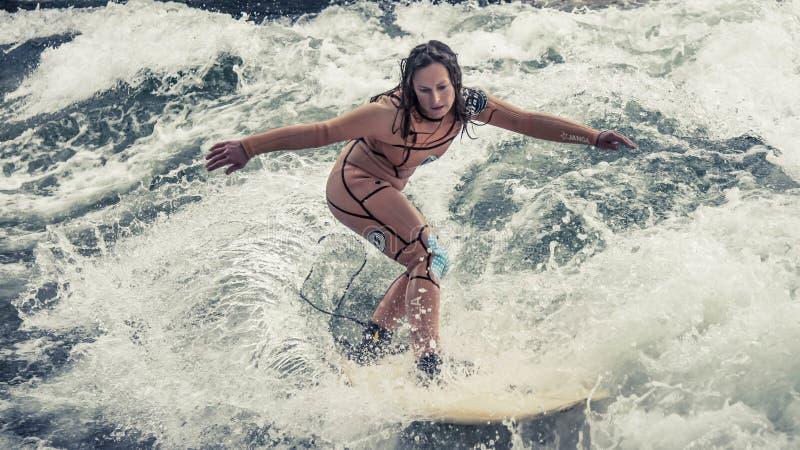 Das Surfen in München bei Englischer Garten ist gefährlich aber möglich: bei einer Kanalkreuzung lizenzfreie stockbilder