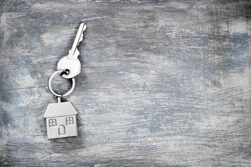 Das Symbol eines Metallhauses mit einem Schlüssel auf einem verkratzten konkreten grauen Hintergrund Platz f?r Text stockbild