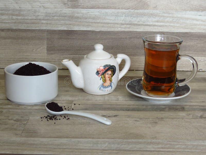 Das Türkische, iranischer, persischer schwarzer Tee im Glas Chai Pulver des schwarzen Tees in einer weißen Porzellanschüssel stockbild