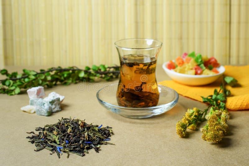 Das türkische traditionelle Glas mit Tee, in der Nähe eine kleine Gruppe des gefüllten trockenen Tees, die türkischen Bonbons und stockbild