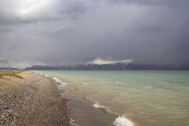 Das Türkiswasser des Sees und die dunklen Wolken vor dem s lizenzfreie stockbilder