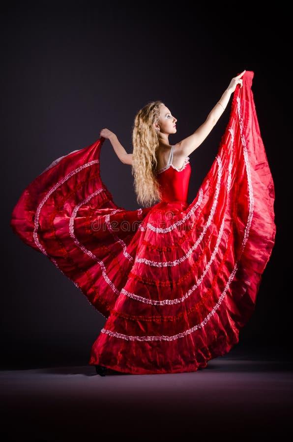 Das Tanzen der jungen Frau im roten Kleid lizenzfreie stockfotografie