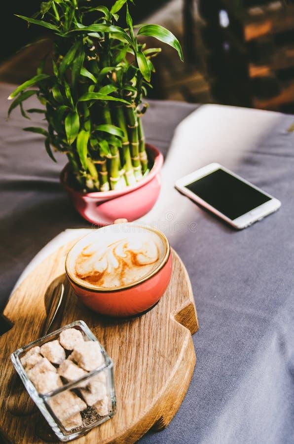 Das Telefon, der Cappuccino, der braune Zucker und ein Vase mit Bambusstand auf dem Tisch lizenzfreie stockfotos