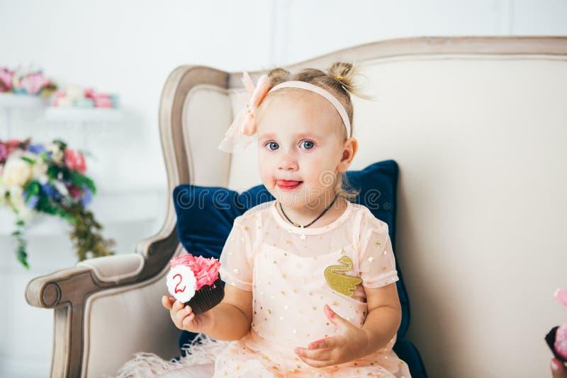 Das Thema ist ein S??speisekuchen mit dem Symbolnummer zwei 2 f?r den Geburtstag eines Kindes Ein kleines Baby sitzt nach innen a stockbilder
