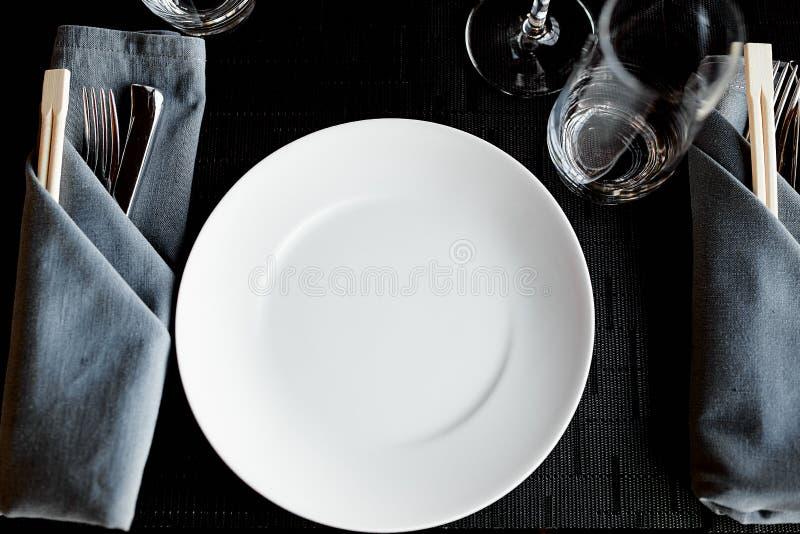 Das Tischbesteck, das in einer grauen Serviette gefaltet werden und eine weiße Platte sind auf dem Tisch lizenzfreies stockfoto