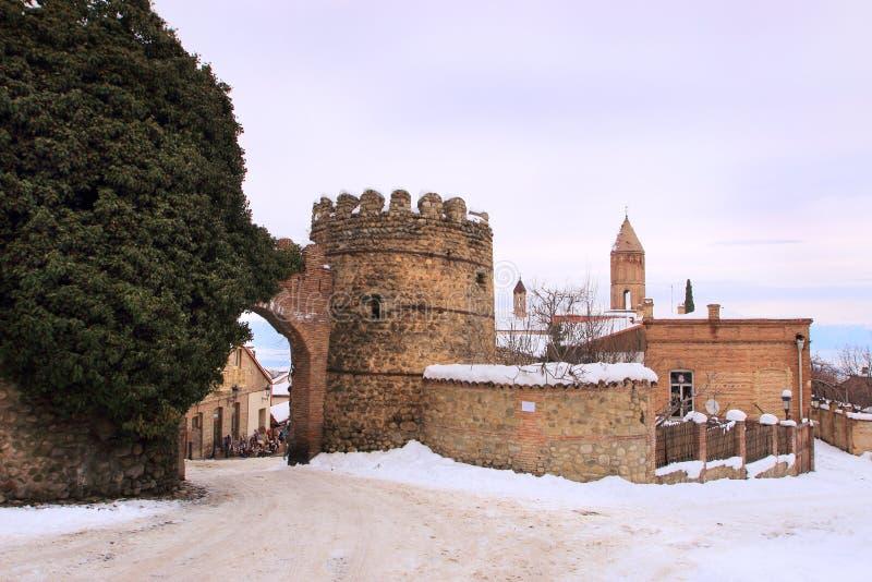 Das Tor, Turm und die Kirche von St George auf dem Hintergrund in Sighnaghi im Winter, Georgia stockfotos