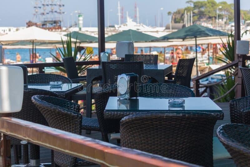 Das touristische Café auf der Küste mit einer Ansicht über Boote im Hafen und Palmen entlang der Küste, Meer, die Türkei stockfoto