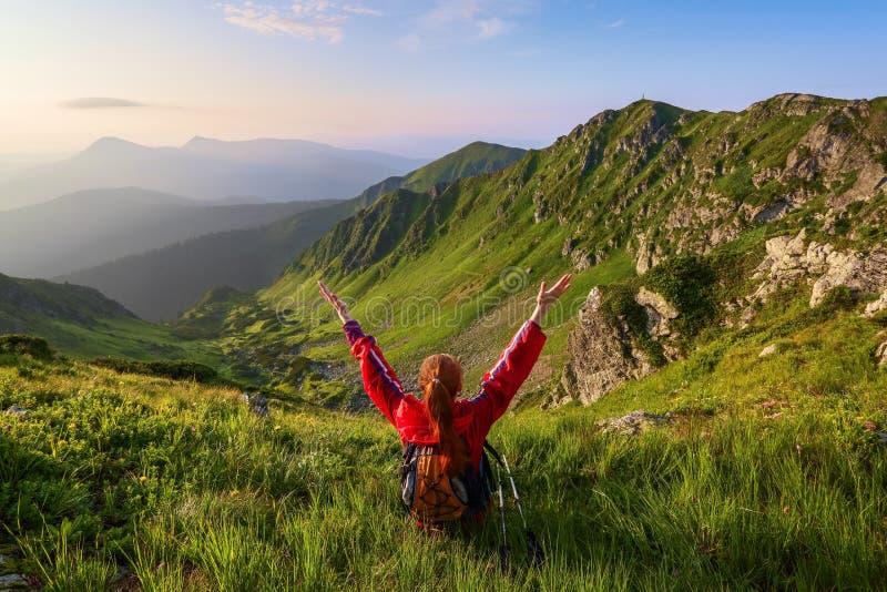 Das touristische Mädchen mit hinteren Sack- und Spurhaltungsstöcken sitzt auf dem Rasen Entspannung Berglandschaften Wunderbarer  lizenzfreie stockfotos