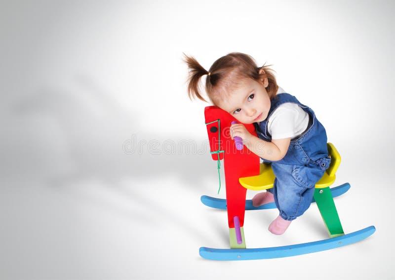 Das Träumen des kleinen Mädchens reitet Spielzeugpferd stockfotos