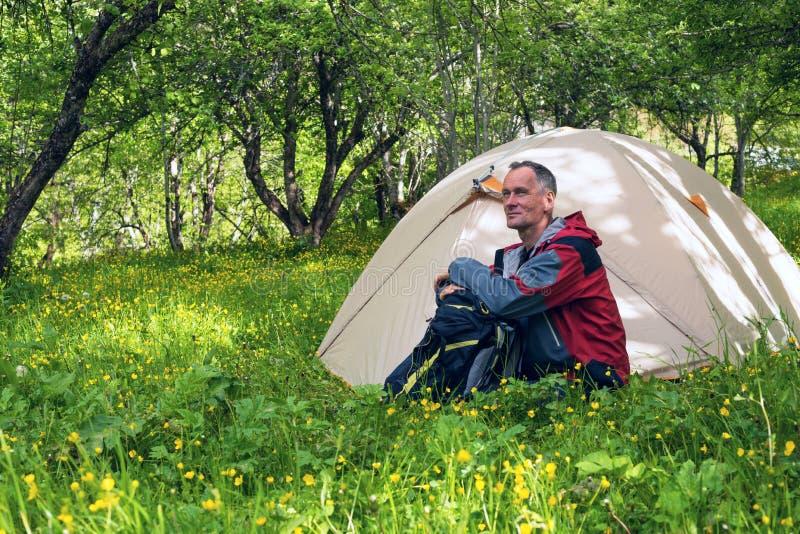 Das Träumen des Reisenden sitzt nahe bei dem Zelt lizenzfreies stockbild