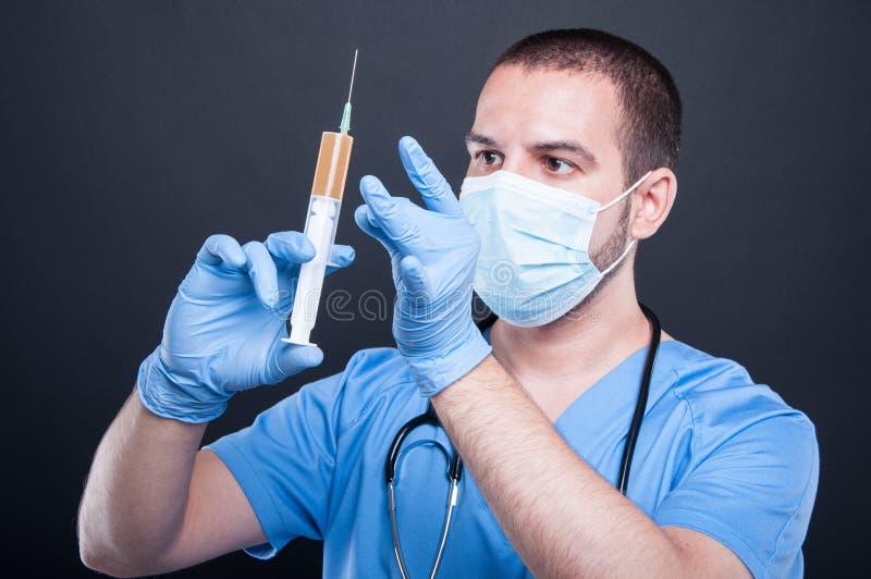 Das Tragen des plastischen Chirurgen scheuert die Prüfung der Spritze stockfoto