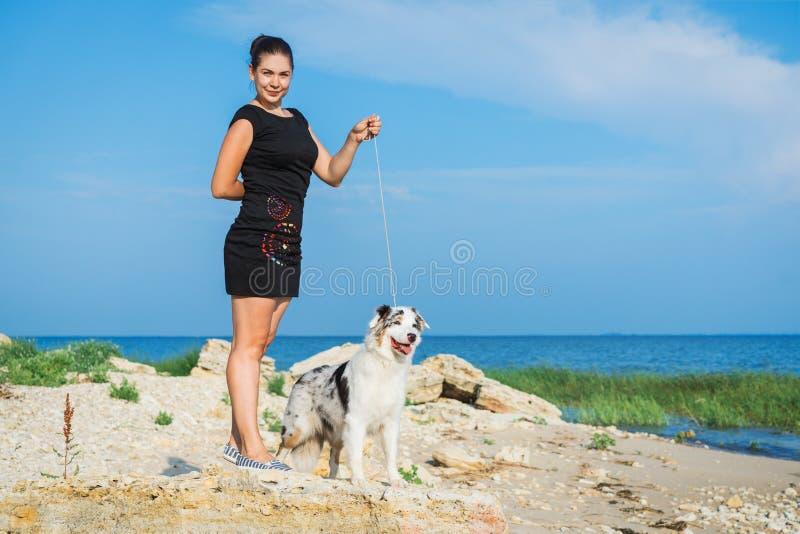 Das Trainermädchentraining mit dem Hundeaustralischen Schäfer-Teamstand, unterrichtet Gehorsam, auf gegen einen blauen Himmel auf stockfoto