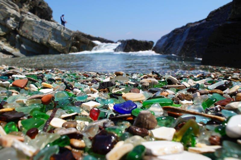 Das Ufer wird mit buntem Glas gestreut stockfotos