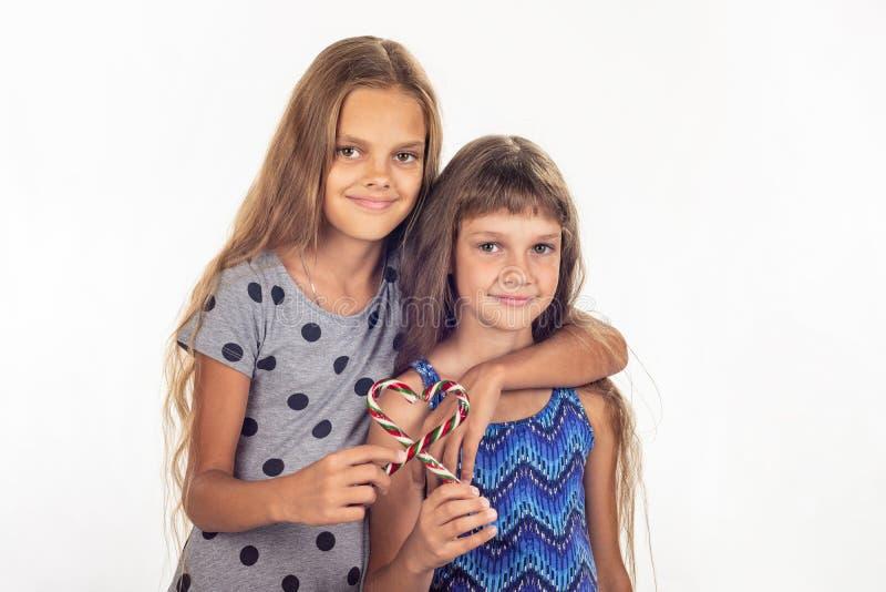 Das Umarmen mit zwei Mädchen machte ein Herz aus zwei Lutschern heraus stockfotos