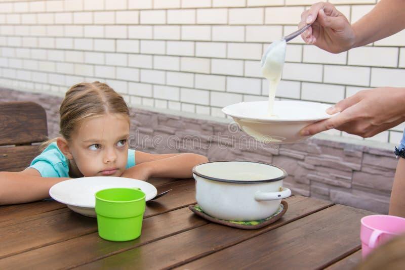 Das umgekippte unzufrieden gemachte Sechsjahresmädchen betrachtet seine Mutter, die Brei zum Frühstück setzt lizenzfreie stockfotografie