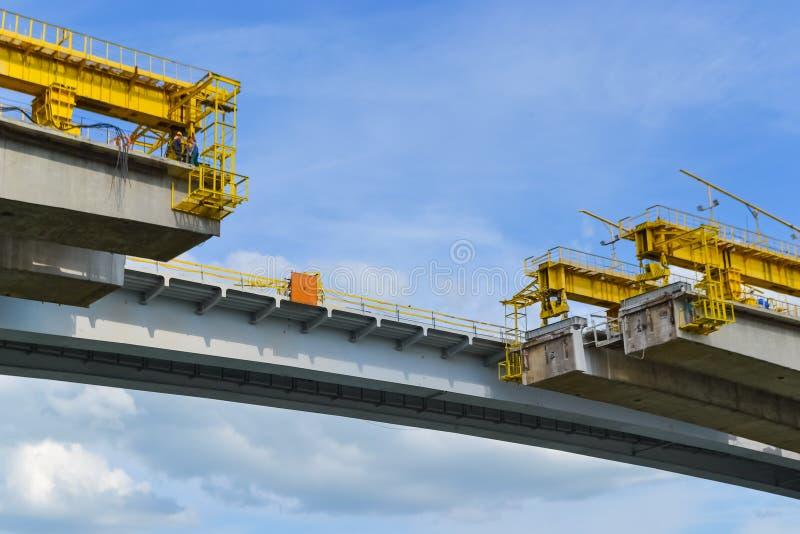 Das unfertige Teil der Straßenbrücke über dem Fluss Rekonstruktion des Teils der Spanne, Arbeit auf Höhe lizenzfreie stockbilder