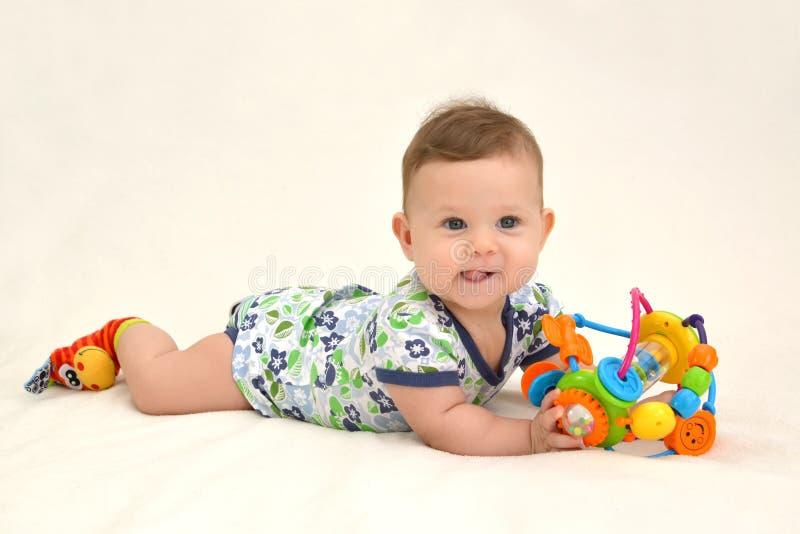 Das unterhaltende Baby hält ein Spielzeug auf einem hellen Hintergrund lizenzfreies stockbild