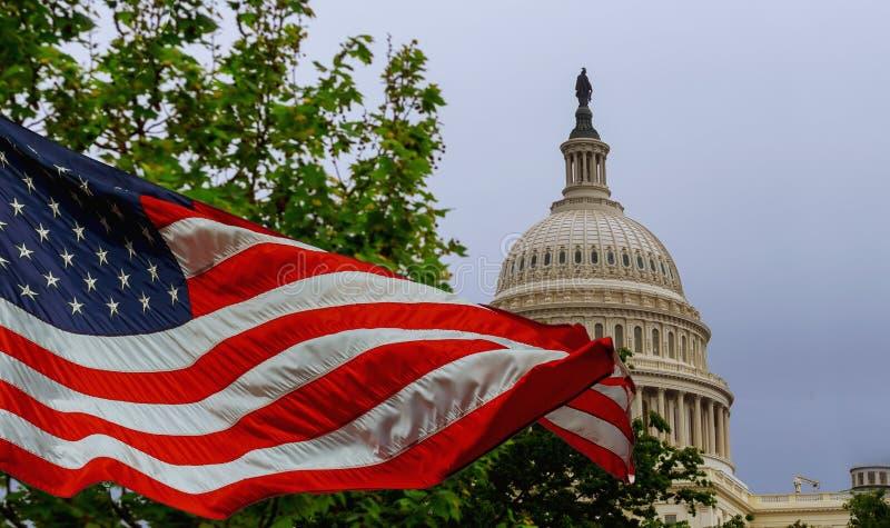 Das US-Kapitolgebäude mit einer wellenartig bewegenden amerikanischen Flagge gelegt auf dem Himmel stockfotografie