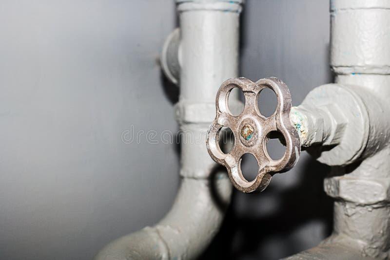 Das Ventil der Wasserversorgungssystemnahaufnahme Kran und Rohre im Keller mit Kopienraum lizenzfreie stockfotos